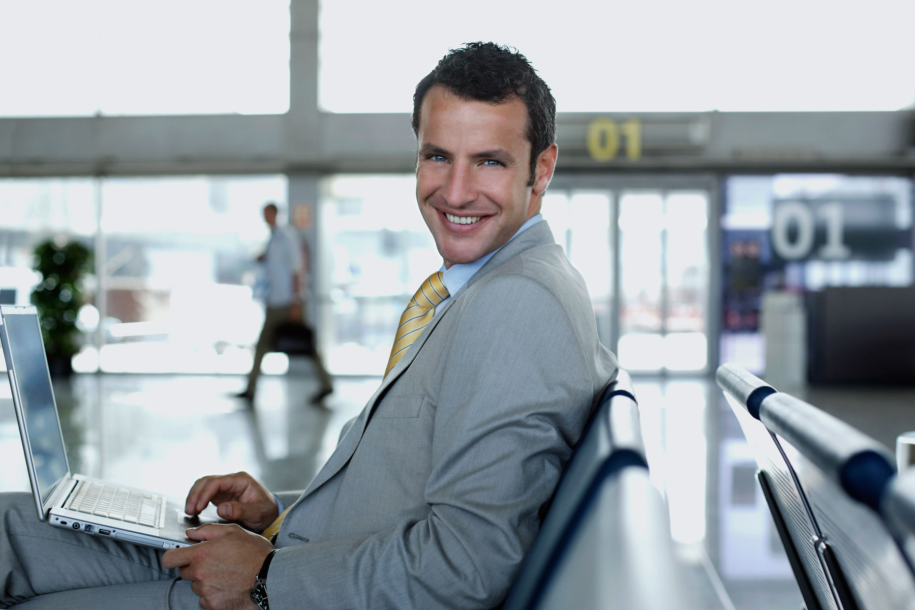 happy bussines man in departure lounge working with laptop